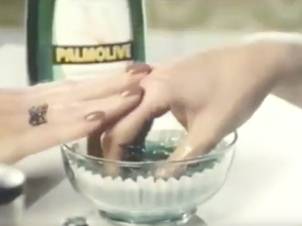 Still from Palmolive ad depicting woman with hand in a bowl of palmolive.