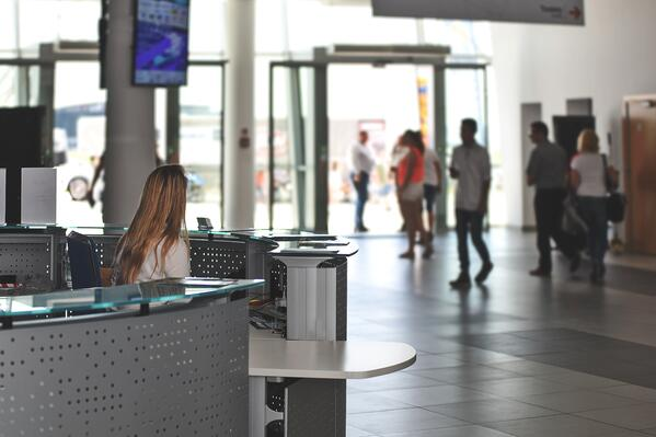 Photo showing woman at large desk with customers in the distance. Customer relationship management software isn't always exciting but it is necessary for many businesses.