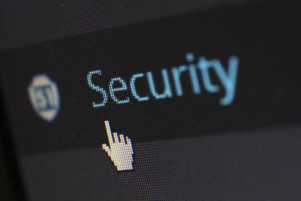 """Picture of a computer mouse hovering over an icon that says """"security"""" on a digital screen."""